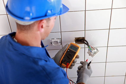 Electrician checking wires in wall socket